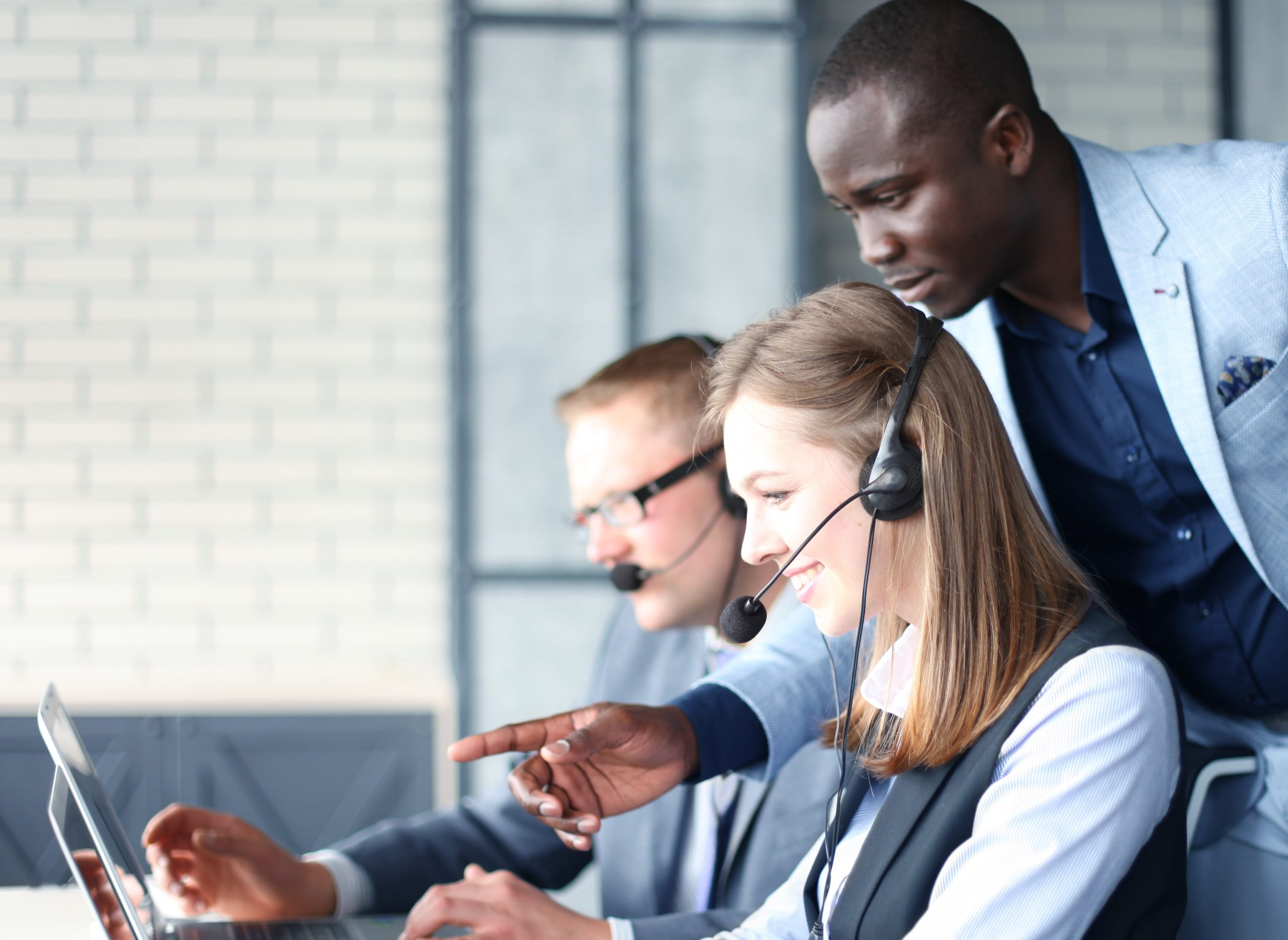 Manager helping call centre employees.